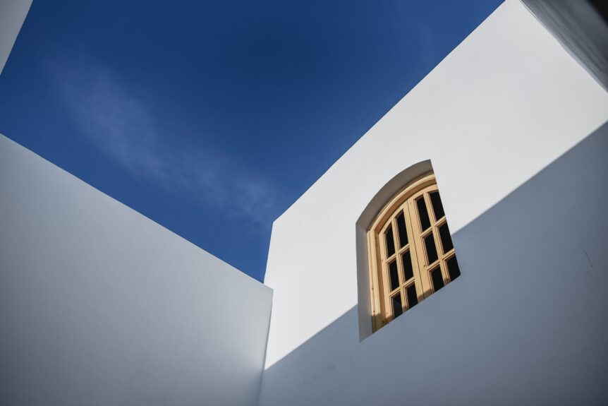 perspective shot of a white wall with window